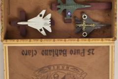 Sin título  Caja de madera, aviones de plástico, cruces de madera y crucifijo metálico  22,4 x 27,8 x 5 cm (abierta)  Colección Familia Ferrari